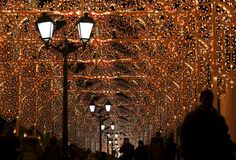 People stroll under festive holiday lights in central Moscow. | (REUTERS/Maxim Shemetov)