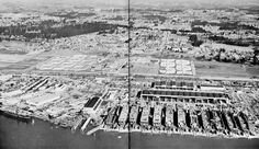 This dramatic view of the Vancouver shipyard during World War II was taken when 12 escort aircraft carriers were in the ways in various stages of completion. At the lower left a carrier is tied up at the outfitting dock. The rectangular building just above the carrier was the cafeteria where thousands of meals were served around the clock. The north-south street in the middle of the photograph is Grand Avenue, with the Maritime Commission's 7,000 bed Columbia House dormitory complex on either side. Just above the intersection with what is now State Highway 14, on the left hand side, is the dormitory's cafeteria which later was purchased by Jantzen Knitting Mills for their local plant. (Photo from National Archives):