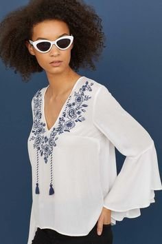 Natural white. Blouse in airy, crinkled, woven viscose fabric with embroidered flowers. V-neck with ties, 3/4-length trumpet sleeves, and gently rounded hem