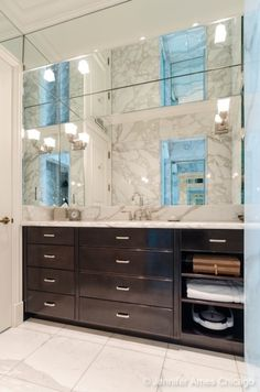 Bathroom with mirror wall above sink and dark wood vanity