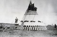 Blackfoot tipi with a very old traditional painted lodge design. Also note the medicine bundle alongside the door, n.d. JE