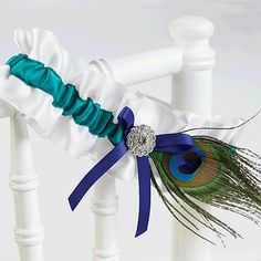 White satin garter with jade satin ribbon and royal blue bow, rhinestone-studded adornment and peacock feather accent.