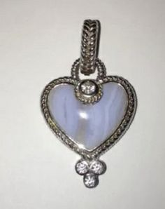 @Frans_Fashions Judith Ripka 925 Sterling Silver Blue Agate Heart Diamonique CZ Enhancer $150.00. Expand your gemstone collection with this brilliant necklace enhancer. A heart-shaped blue agate gemstone shines with a textured, rope-style border. The enhancer is accented with round, bezel-set Diamonique (simulated diamonds). Three at the bottom and one at top center of heart.  This heart is no longer being made. Collectors item. Judith Ripka, Agate Gemstone, Heart Shapes, Diamonds, Pendant Necklace, Gemstones, Sterling Silver, Top, Blue
