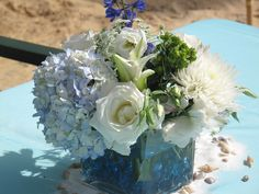 """AQUA LINENS.  LIGHT BLUE HYDRANGIA, DARK BLUE DELPHINIUM, WHITE TIBET ROSES, WHITE ASTROMERIA, QUEEN ANNE LACE, ORIENTAL LILIES, SPIDER MUMS, DOUBLE LISIANTHUS, GREEN HYPERICUM NESTLED IN BLUE GLASS STONES IN CLEAR 8"""" SQUARE PLACED ON WHITE SAND SCATTERED WITH GLITTER AND SEA SHELLS."""