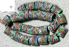 Trade Beads | A strand of rare and superb cylindrical Venetian millefiori beads used for the African trade. | The canes core is dark green, the canes brick, white, navy and green and the band around the center is the same color as the canes