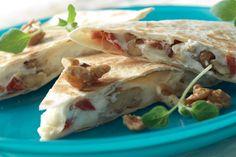 Zachtzoute geitenkaas met zoete honing en knapperige walnoten in een gegrilde tortilla.