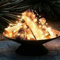 Keep a Firepit glowing all season with solar-powered Copper-Wire Lights loosely draped over a pile of Wooden Logs in a Cast Iron Fire Bowl.