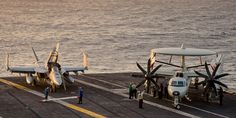 """A Boeing F/A-18F Super Hornet, from Strike Fighter Squadron 41 (VFA-41) """"Black Aces,"""" and a Northrop Grumman E-2C Hawkeye, from Carrier Airborne Early Warning Squadron 112 (VAW-112) """"Golden Hawks,"""" resting on the flight deck of the USS John C. Stennis (CVN 74) as the sun begins to set.  www.ottosenphotography.com 