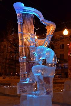 The street lights shine golden light through this Ice sculpture of a musician bent over playing a huge Harp of Ice. -DdO:)