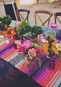 This whimsical, southwestern tablescape is perfect for a destination wedding! Pinks, greens and oranges brighten up the dark tables, we're in love.