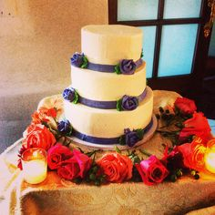 Here is a 3 tier cake made out of soft butter cream frosting with purple ribbon an purple flowers made out of butter cream frosting.