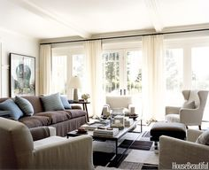 Ample and comfortable seating in earth-tone linens with cashmere pillows and throws creates a serene setting, while sheer curtains keep it light and easy. Designed by Robert Stilin.   - HouseBeautiful.com