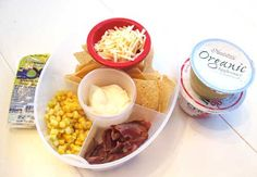 Easy lunch box ideas: tortilla chips with corn, bacon, cheese, sour cream and guacamole; and cups of applesauce and raspberry yogurt. Http://www.LunchBoxBlues.com