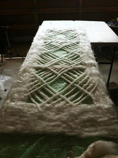 A scarf before the wool roving is layered and woven, ready to felt with soap, water, and pressure.