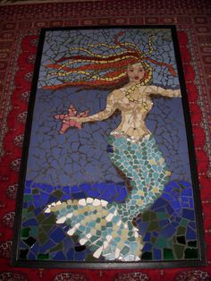 https://flic.kr/p/8EEVu8 | Mermaid and Pink Star | I discovered the Habitat for Humanity Restore. Tons of tile pulled out of old homes, great colors, and super cheap. The gold in her hair was recycled 60's kitchen tile. The blues and greens in her tail, also recycled from H.4 H. Much of the torso is recycled floor tiles. Several old thrift store plates used in the hair and background.