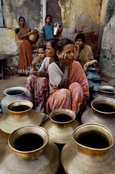 Women waiting to fill their brass pots with water 1983. India by Steve McCurry