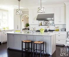 The neutral setting of an all white kitchen is a positive feature that feels easy to live with. A combination of stainless-steel appliances, crisp white cabinets, a large island, and hardwood floors creates an appealing work space for any family. The gray-blue color of the island acts as an exciting neutral in the space.