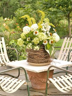 Green Goddess-A vase set in a stack of grapevine wreaths is filled with cool white-and-green tinted foliage. Hydrangea mingles with white coneflower, variegated hosta leaves, and yellow spires of foxtail lily.