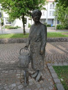 This is a figurative public sculpture of a 'Woman with Basket' located at the Schlossplatz in Hüfingen, Germany, Baden-Württemberg.