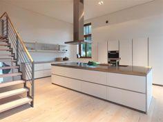 Strakke witte keuken met kookeiland. Liefhebbers van een moderne, strakke keuken komen helemaal aan hun trekken met deze prachtige b1 keuken van bulthaup. Het enorme kookeiland beschikt over diepe, brede lades waar je met gemak alle kookbenodigdheden in kwijt kunt. Doordat de keuken greeploos is, is hij nog strakker. De bovenkastjes hebben geen deuren, maar zijn voorzien van melkglazen schuifdeuren. Dit houdt het geheel open.