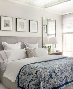 Elegant bedroom features art gallery over gray velvet headboard accented with silver nailhead trim, white and blue hotel bedding as well as white and blue blanket next to mirror over light taupe wood waterfall bedside table.