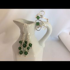 Emerald Ring and Earring Set This beautiful set is made up of a sliver wire wrap ring with green Swarovski crystals and a lovely pair of green dangle earrings, also made with sliver wire and emerald green Swarovski crystals. This set is so stunning in the sunshine, they really sparkle! Becky Barnes Designs Jewelry Earrings
