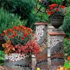 "Create Mosaic Magic in Your Garden | Midwest Living 8, 10, 18"" diameter PVC pipes cut to varying heights - cover with mosaic pieces.  Overturned terra cotta saucers on the top.  Like the garden sculpture on top!"