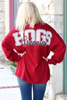 "Calling all Arkansas Razorback fans! This super cute jersey is for you! Long sleeve with thumb holes. These are thicker than a t-shirt but lighter than a sweatshirt. Back features ""HOGS"" in all caps with a seersucker print inside. ""Arkansas"" in cursive across the back. The front features the Razorback logo on the left chest. These are larger fitting than a t-shirt."