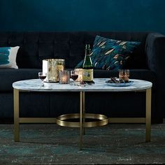 """Marble Oval Coffee Table #westelm mooth and cool with a subtle gleam. We topped an architectural metal base in an antiqued brass finish with a sturdy marble slab to create this sculptural coffee table that sits well with other luxe materials, like silk and velvet. $499 42""""w x 24""""d x 18""""h. Solid marble top. Metal bottom in an Antiqued Brass finish."""