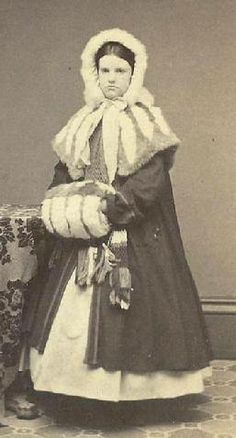 Scarf under cape, muff, coat, hood with tippets on cape.