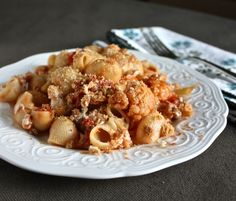 Pasta with Cauliflower, Sausage, & Breadcrumbs  serves six to eight  2 tablespoons olive oil  1 large shallot or small onion, diced  2 cloves garlic, minced  1/2 pound sweet Italian sausage  1 head cauliflower, cut into small, bite-sized florets  2 14.5-ounce cans diced tomatoes  1 pound pasta (ours are lumaconi; rigatoni, ziti, penne, or farfalle would all work)  1/2 to 3/4 cup fresh breadcrumbs  1/2 pound fresh mozzarella, cut into 1/2-inch cubes