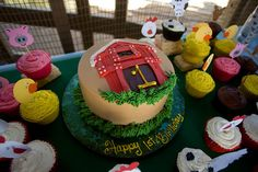 Adorable farm themed cake for first birthday party! Love that barn and all the cupcakes!