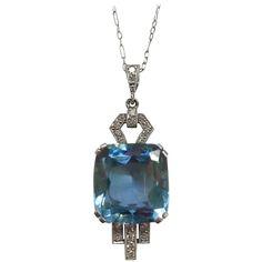 1920s Aquamarine Diamond Platinum Pendant. 1920's platinum pendant set with circular-cut diamonds and a cushion shaped aquamarine.  On a delicate platinum original chain.