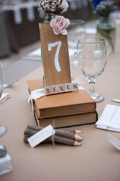 picture the books as cracker jack boxes with the old fashion baseball print on top with a table number as the center piece with flower arrangements