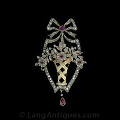 A lovely Victorian / Edwardian transitional design, this sparkling bouquet of flowers is framed in diamonds with a ribbon on top. The flower stamens and bow knot are of bright red rubies and a dangling pear shape ruby finishes the elaborate design. Numerous rose cut diamonds set in silver and silver over yellow gold.