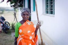 woman sweeping - A woman poses with her broom while smiling in Kampalapura, India.