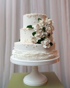 This three-tiered, two-flavored confection was adorned with gardenias (the bride wore a fresh one in her hair), sugar pearls, and ruffles. It sat atop a pedestal and was showcased within a large wooden frame.