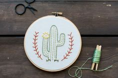 :: Adorable cactus handmade in USA embroidery art. Made using cotton thread and is stitched onto unbleached muslin fabric. It is stretched on an 6-inch wooden embroidery hoop that is perfect for hangi