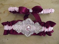 Wine and pink satin #wedding #garter set banded in pink and accented with a rhinestone and #crystal applique.  The applique is centered with a pink stone accented with silver ... #bride #bridal #weddings #ido #bridalgarter #weddinggarterbelt #applique ➡️ http://jto.li/B62H9