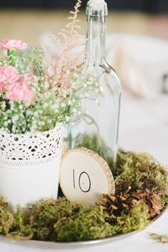 Vintage garden table arrangements. Place some roses and filler flowers in pot, add some white doilies and a wine bottle by its side and voilá! Vintage chic and really affordable.