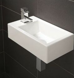 Small cloakroom sink on wall of black tiles