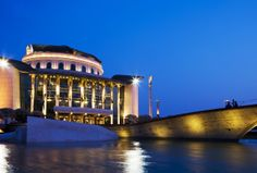 With a striking almost-circular shape, the National Theatre opened in 2002 on the bank of the Danube as home to Hungary's most prestigious stage. Look for the reflecting pond where the upper façade of the Old National Theatre rests submerged in the water. National Theatre, Luxury Accommodation, Four Seasons Hotel, Modern Buildings, Hungary, Budapest, Pond, Facade