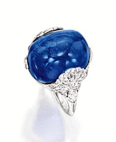 SAPPHIRE AND DIAMOND RING. Centring on a cabochon sapphire weighing approximately 22.60 carats, to a stylised mount set with marquise-shaped and circular-cut diamonds, mounted in platinum.