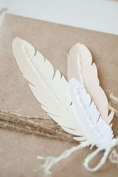 white paper feathers on brown kraft paper gift wrap