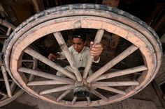 A boy prepared a wooden wheel to be used on horse carts in Peshawar, Pakistan, Tuesday. World Day Against Child Labor will be observed on Wednesday. (European Pressphoto Agency)