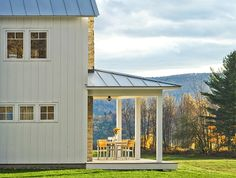 Board and batten siding, a large, low-to-the-ground porch and standing seam metal roof. Now that's modern farmhouse style!