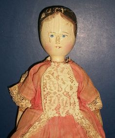 """Large antique wooden peg doll. Measuring 15"""" tall. The doll shows wear but I think she is wonderful. She has a wood carved lathe turned head with black painted hair and a lighter shadow around the front of her hair. Blue painted eyes with black pupils and black painted liner and brows. A carved nose and red painted mouth and accent under the nose. Still retains her rosy cheeks. She has a wood carved jointed body. Spoon carved hands and black painted flat shoes."""