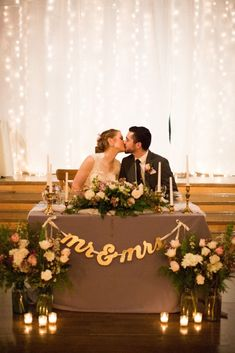 Green Villa Barn just 10 min from downtown Salem Oregon. Twinkle light backdrop of kissing bride and groom at sweetheart table with gold mr and mrs banner and candles gold candlesticks. Wonderful Salem Wedding venue