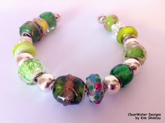 Green Cuff Bracelet European Style Large by ClearWaterDesignsbyK, $24.95 http://clearwaterdesignsbyk.etsy.com http://clearwaterdesigns.info This is a Classic looking European Style Large Hole Lampwork Bead, Cuff Bracelet. I've used High Quality European Beads in Greens & Yellow & accented with Silver Toned Spacer Beads & Enamel Rondelles.The cuff as well as the cores of all Lampwork Beads are Silver Plated.   This Green Cuff Bracelet would be great to wear for St. Patrick's Day!