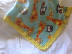 Blue fleece blanket with giraffes and owls and a yellow crocheted edging